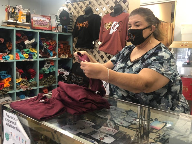 Imelda Ramirez, owner of Action Sports and Awards, prepares for Small Business Saturday.