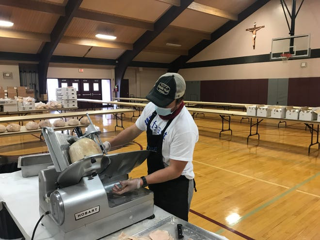 Volunteer John Morgan Clauss slices turkey as part of preparing more than 3,000 Thanksgiving meals handed out at a Warrington church Wednesday.