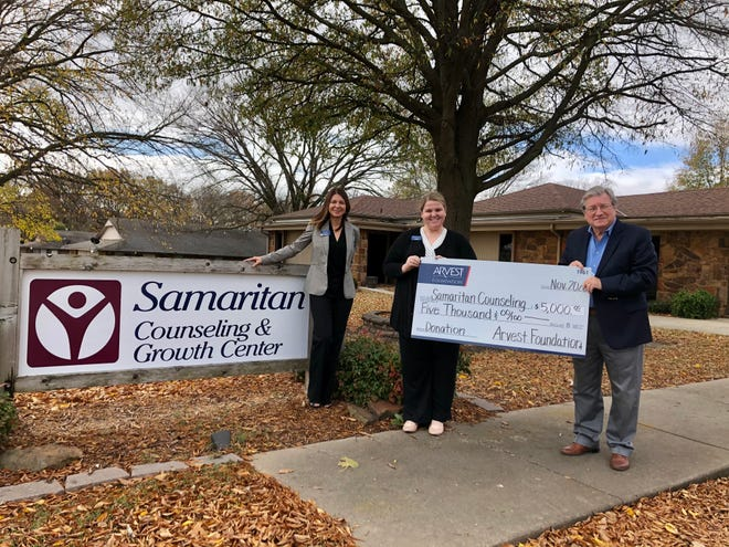 Arvest Bank president Kim Adams and sales manager Whitney Watson present a check to Larry Cowen, executive director of Samaritan Counseling.