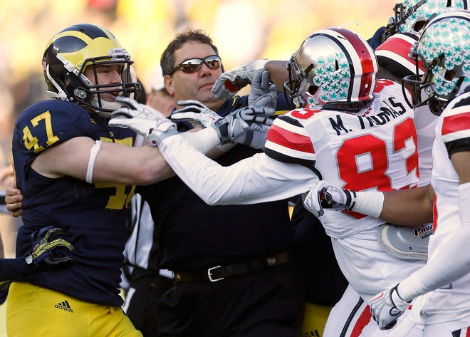 In 116 meetings, there has been plenty of bad blood between the Ohio State and Michigan football teams. In this 2013 photo, Michigan coach Brady Hoke tries to break up a spat between Wolverines linebacker Jake Ryan (47) and OSU receiver Michael Thomas (83).