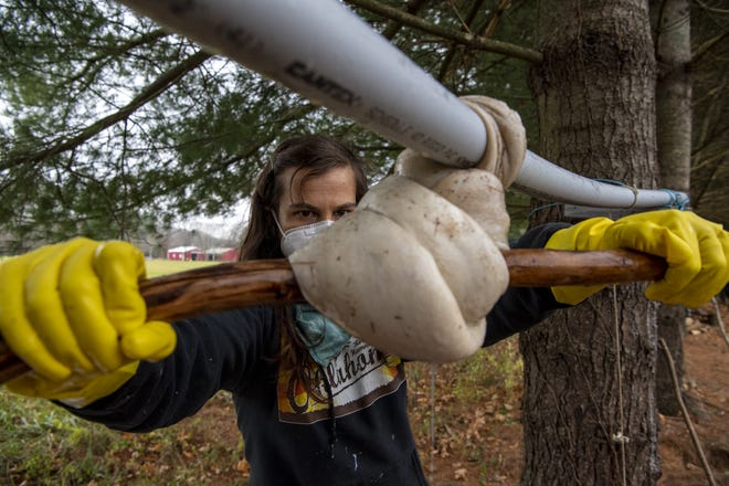 Talcon Quinn squeezes the brain tan solution out of a deer hide, using a stick to create torque, during a workshop she hosted in her backyard near Athens.