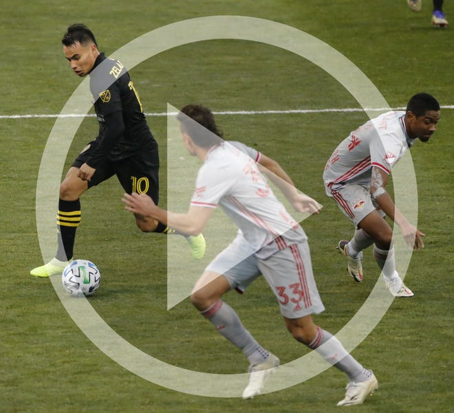In this file photo, Columbus Crew SC midfielder Lucas Zelarayan (10) dribbles around New York Red Bulls defender Jason Pendant (24) and midfielder Aaron Long (33) during the second half of the MLS Cup playoff match at Mapfre Stadium in Columbus on Saturday, Nov. 21, 2020. The Crew won 3-2.