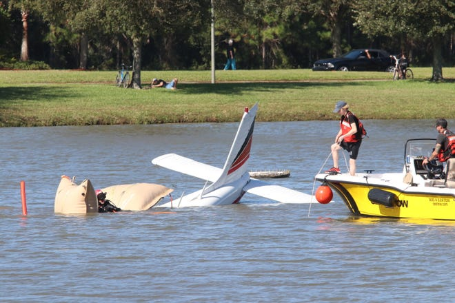 Workers begin to pull a small plane out of a retention pond near Airport Road in the Venetian Bay community of New Smyrna Beach on Wednesday, Nov. 25, 2020. The plane crashed Tuesday evening, with the pilot and passenger suffering minor injuries.