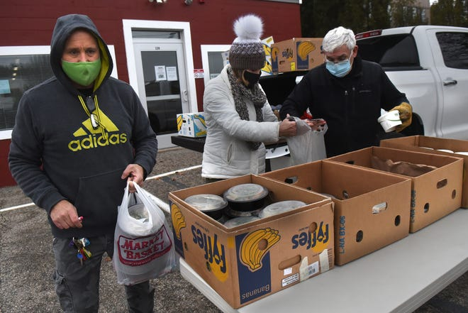 Dover Triangle Club's Mike Dorely, left, Michelle Murch and Bob O'Connell put together Thanksgiving meals for drive-through service Wednesday, Nov. 25, 2020.