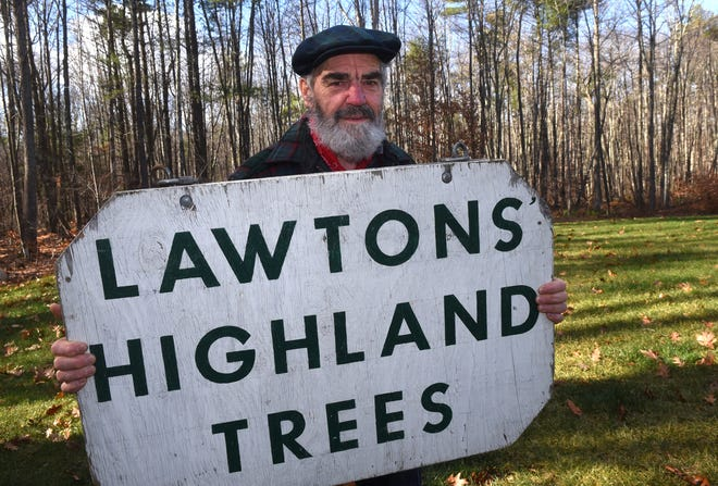 Ron Lawton holds the sign he's had at his Christmas tree stand for the last 14 years at Eliot Commons, where he made longtime customers and friends. He has retired and says he will miss the business and the people very much.