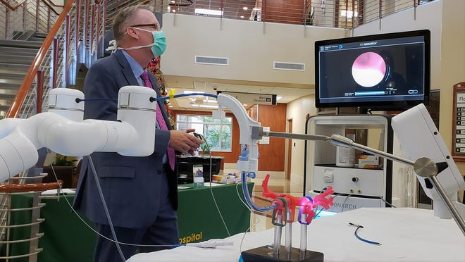 Dale Mueller, head of cardiovascular and thoracic surgery at Memorial Hospital Jacksonville, maneuvers a new robotic-assisted bronchoscopy system through a simulated bronchial tube (center) as its built-in camera shows the way on the screen.