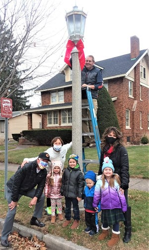 Larry Knuth (on the ladder), Sue Knuth on the right are Prairie Street captains leading volunteers to put up holiday bows.  George and Mary Burgland are on the left. The Knuth grandkids at the bottom are from right to left: Avery, Connor, Grayson, and Madalyn (under Mary) Knuth.