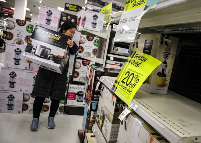 In this Nov. 29, 2019 file photo, a shopper carries a Crock-Pot during Target's Black Friday sale in New York. The National Retail Federation, the nation's largest retail group, expects that holiday sales could exceed growth seen in prior seasons despite the uncertainty surrounding the pandemic. (AP Photo/Bebeto Matthews, File)