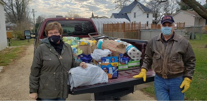 Lake Carroll Association members recently donated two truck loads of food and nearly $1,000 in cash to the Shannon-Lanark Food Pantry. Pictured, from left: Deb Foust and Cliff Mortenson.