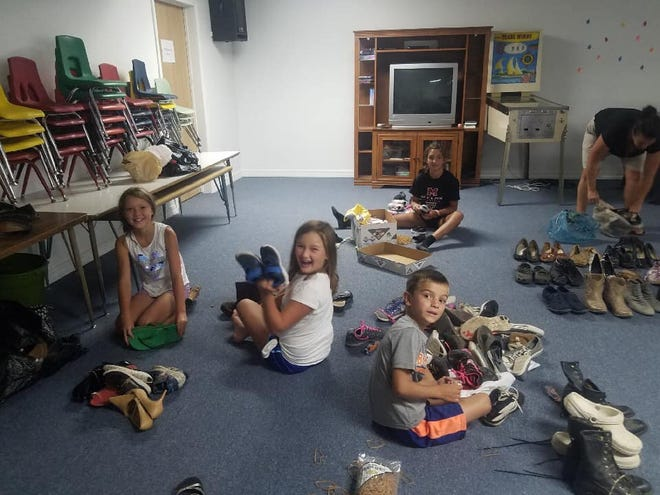 Youth volunteers Presley, Avalon, Nolan, Adi, Gina and Roni sort through shoes for their ongoing shoe drive fundraiser.