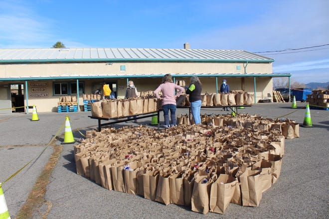 Siskiyou Food Assistance volunteers stand amid a sea of grocery bags ready to be dispersed to those in need Monday morning in Weed. All together, nearly 500 meals were donated.