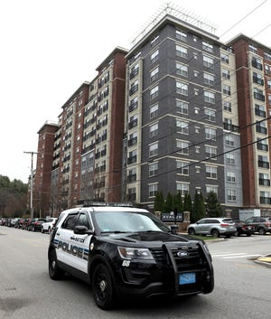 A Natick police cruiser passes by the Avalon Apartments at 1 Chrysler Road in Natick on Wednesday, Nov. 25, 2020.
