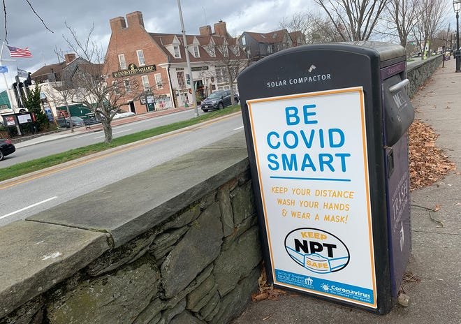 A sign in downtown Newport reminds people to wear masks and remain socially distant. The city added 66 new cases of COVID in the past week.