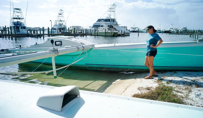 Captain Pam Kane stands by the hulls of her previous boat that was seriously damaged by Hurricane Sally.