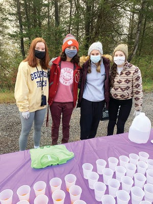 Members of the Swim team volunteer at the Secret City Half Marathon that was held on Melton Lake Drive in Oak Ridge. Pictured from left to right are Genevieve Krass, Carter Valencia, KelliAnn Corbett and Amelia Hodge.