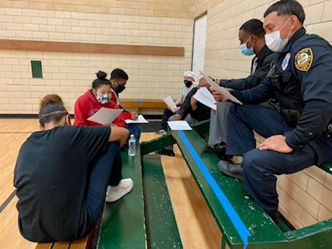 Utica police Investigator Mike Washington, left, and Officer Jimmy Dongsavanh, right, speak with students during a meeting of the Utica police's newly created police athletic league.