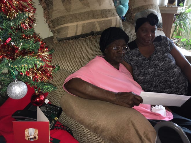 Essie Wright, left, looks over a check from Community With a Heart last year. Her daughter, Wanda Follins, sits next to her.
