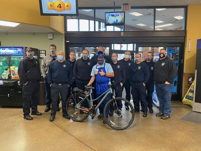 Jerry Harrison of Pekin (front) admires the new bicycle presented to him by Pekin firefighters to replace his stolen wheels.