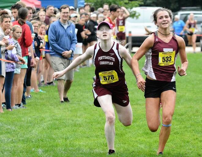 Portsmouth Christian Academy's Liza Corso, left, races to the finish line during the 2018 Bobcat Cross Country Invitational in Madbury.