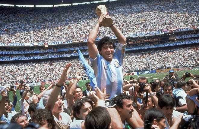 FILE - In this June 29, 1986 file photo, Diego Maradona holds up his team's trophy after Argentina's 3-2 victory over West Germany at the World Cup final soccer match at Atzeca Stadium in Mexico City. The Argentine soccer great who was among the best players ever and who led his country to the 1986 World Cup title before later struggling with cocaine use and obesity, died from a heart attack on Wednesday, Nov. 25, 2020, at his home in Buenos Aires. He was 60. (AP Photo/Carlo Fumagalli, File)