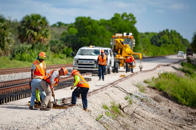 Brightline construction crews position a rail north of Hood Road on Aug. 7 in Palm Beach Gardens. Brightline is adding a second set of tracks for their planned expansion to Orlando.