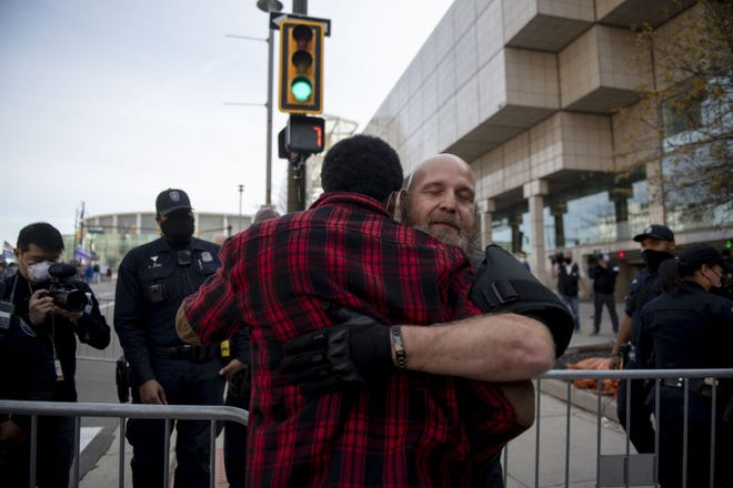 Counter protester Jacob Webster, back to camera, of Detroit, embraces Phil Robinson, a member of Michigan Liberty Militia, after the two debated about President Donald Trump across a barricade during a protest outside the TCF Center in Detroit on Nov. 6.