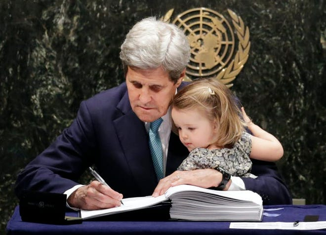 Then-Secretary of State John Kerry held his granddaughter as he signed the Paris climate agreement in 2016. [AP Photo/Mark Lennihan]