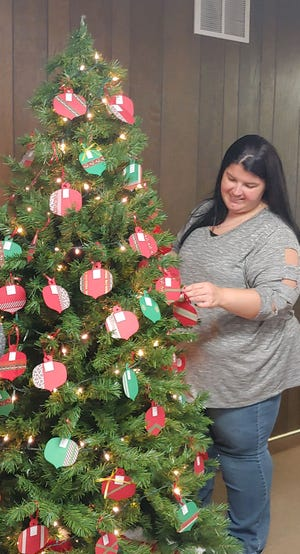 Alica Bustamante of the ElderCare staff decorates the Giving Tree at the non-profit agency's office in Great Bend.