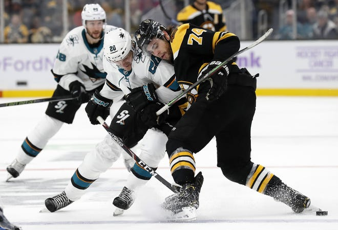 Bruins forward Jake DeBrusk leans on San Jose's Marcus Sorensen as they battle for the puck during a game in October 2019 at TD Garden. DeBrusk intends to record more hits during the upcoming season than he has in the past and is working on bulking up .
