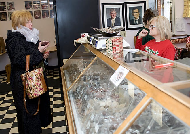 Sue Grove, right, assists Mary Kay Faunda, who in November 2019 made the trip from Younstown to purchase candy for Christmas gifts at Heggy's in Alliance.