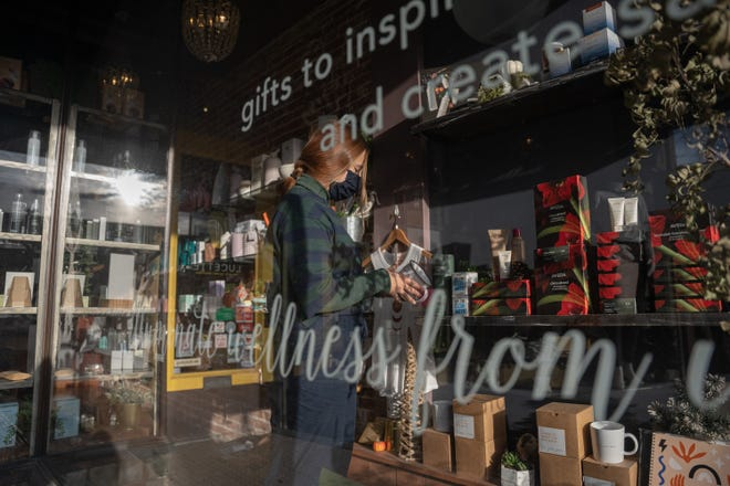 Receptionist Gretchen Stark tidies products displayed on store shelves at Lucette Holistic Salon & Boutique on Friday, Nov. 20, 2020, in Rockford.