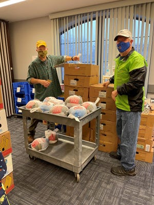 Pictured, from left, are Evan Evans of the Colchester Rotary Club and Alan Hurst of the East Hampton Rotary Club as they gather turkeys for distribution to town residents.