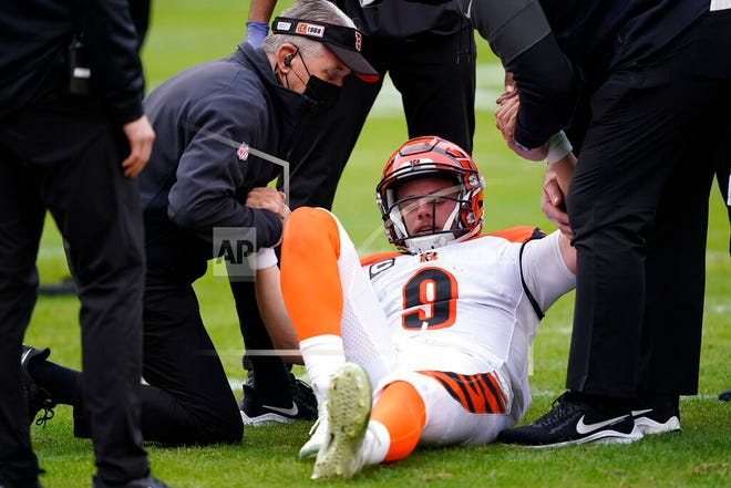 Cincinnati Bengals quarterback Joe Burrow is helped getting off the field during the second half of an NFL football game against the Washington Football Team, Sunday, Nov. 22, 2020, in Landover. Bengals rookie suffered a left knee injury during this play and was carted off the field.
