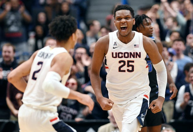 Connecticut's Josh Carlton (25) reacts toward teammate James Bouknight (2) after making a basket during the first half of the team's NCAA college basketball game against Memphis, Sunday, Feb. 16, 2020, in Hartford, Conn.