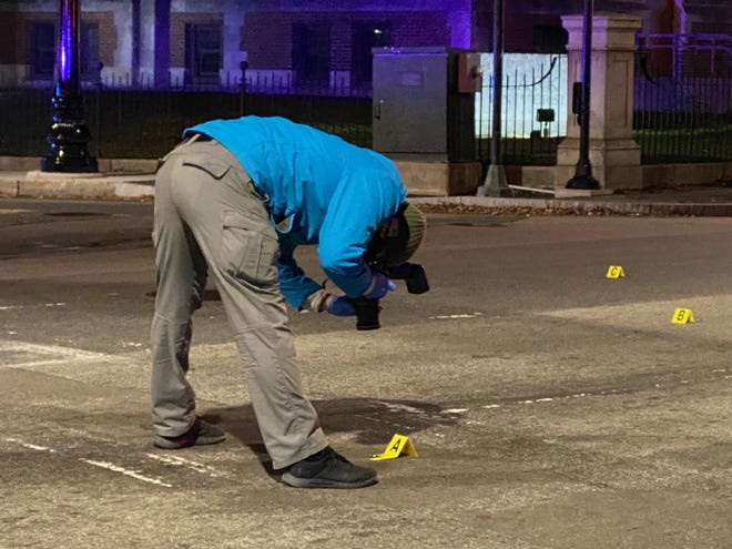 A police crime scene investigator photographs evidence after a report of shots being fired near Main and Crystal streets in Main South in Worcester late Tuesday night
