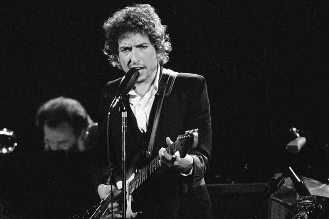 Musician Bob Dylan performs with The Band at the Forum in Los Angeles on Feb. 15, 1974.