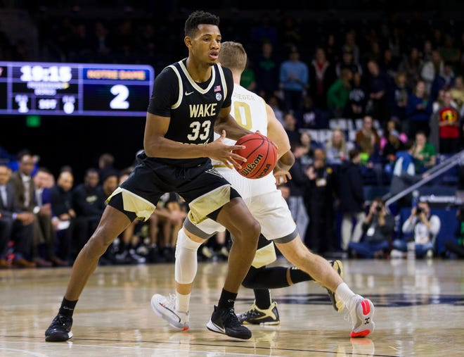 Wake Forest forward Ody Oguama, front, moves by Notre Dame's Rex Pflueger during a game last season.