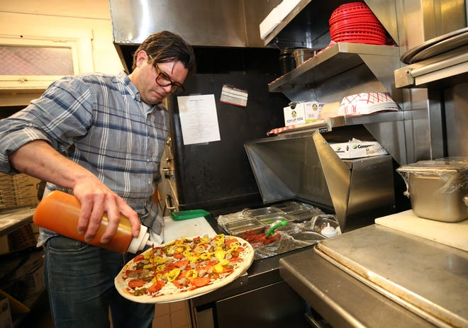 Doug Sauer makes his Firefighter Pizza on Nov. 23 at the Hey Hey Bar & Grill, where he leases the kitchen to operate Alberta's Pizza Kitchen.