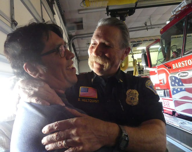 """Barstow Assistant Fire Chief Sid Hultquist embraces Louis """"Rooster"""" Abeita Jr. during a reunion on Monday, Nov. 23, 2020, in Barstow. Nearly 34 years ago, when Abeita was 4 years old, Hultquist helped save his life."""