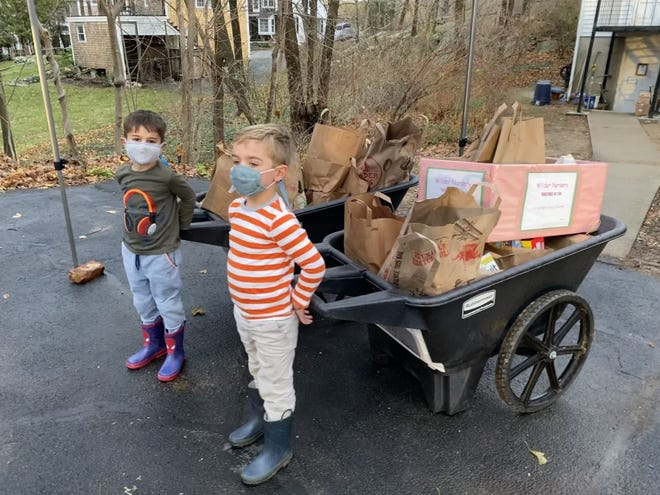 Xavier Dunn (left) and Charlie Herrlinger, both of Hingham, help deliver food donated from families at the Wilder School to the Hingham Food Pantry.