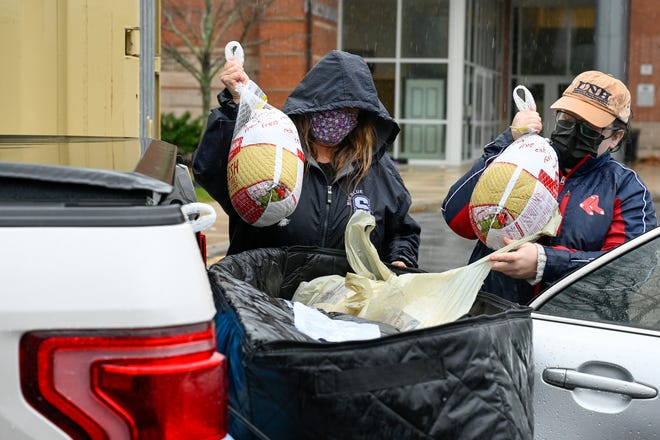 Laura Coppola, left, President Anchor Food Pantry, and Kayla LeClerc, right, Anchor Food Pantry board member, grab turkeys from the bed of this pick up truck during the Swampscott area Anchor Food Pantry Thanksgiving meals distribution program behind the Swampscott High School on Monday, Nov. 23, 2020.