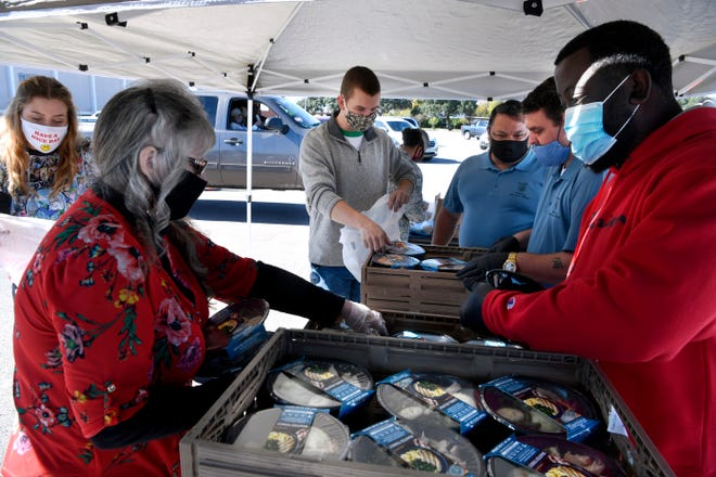 "Volunteers give out Thanksgiving dinners in the north parking lot of the Abilene Convention Center on Wednesday. The Thanksgiving Day ""Feast for All"" was organized by the Taylor County Veterans Service Office and was held in the parking lot to minimize exposure risks from COVID-19. Bryan Massey, the director of the office, said they had approximately 1m000 meals they were giving away."