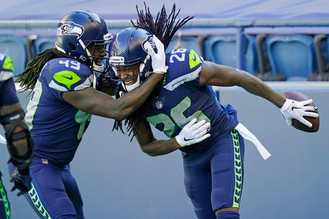 Seattle Seahawks cornerback Shaquill Griffin (26) is greeted by his twin brother, outside linebacker Shaquem Griffin (49), after a September interception.