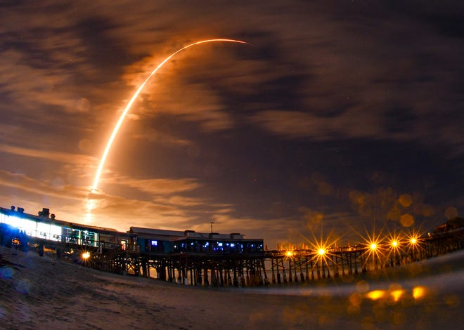 A SpaceX Falcon 9 rocket is seen from the Cocoa Beach Pier as it launches the company's 16th Starlink mission from Cape Canaveral on Tuesday, Nov. 24, 2020.