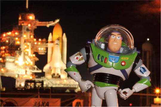 Buzz Lightyear poses with space shuttle Discovery