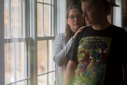Pam Warfle stands with her son Jonathan Warfle, who is recovering from a bout of COVID-19.