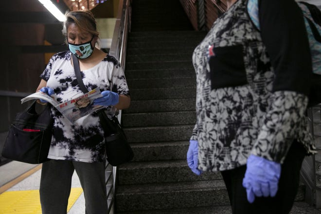 Wanita dengan masker wajah dan sarung tangan pelindung menunggu kereta Metro Rail di Los Angeles.