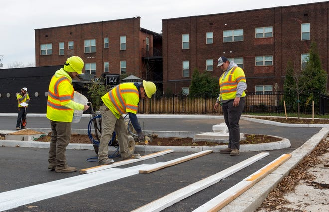 Workers with RoadSafe Traffic Systems strip the newly redesigned intersection at Washington Avenue and Second Street near Haynie's Corner Tuesday afternoon, Nov. 25, 2020.