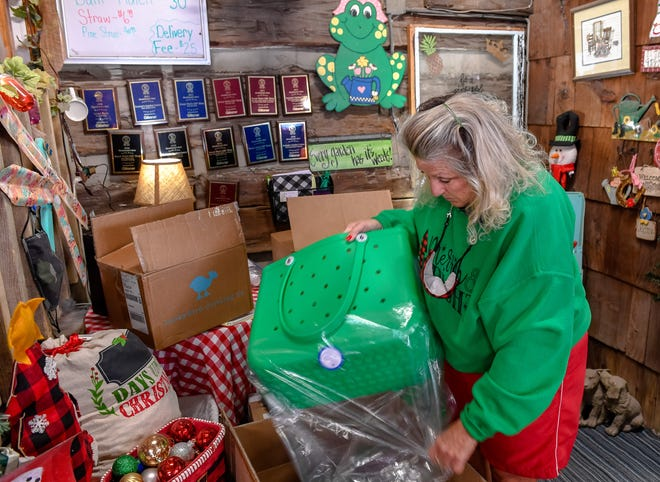 Owner Audrey Benton unpacks a shipment off Bogg tote bags, one of this season's big sellers at Henderson's Sweet Pea's Gift Shop Tuesday, November 24, 2020.