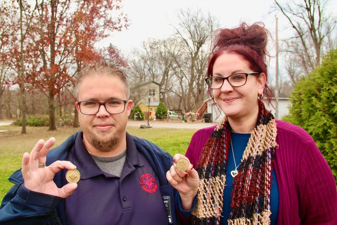 Dock, left, and Lori Henry show their four-year sobriety coins earned from their participation in Narcotics Anonymous recovery programs and meetings.
